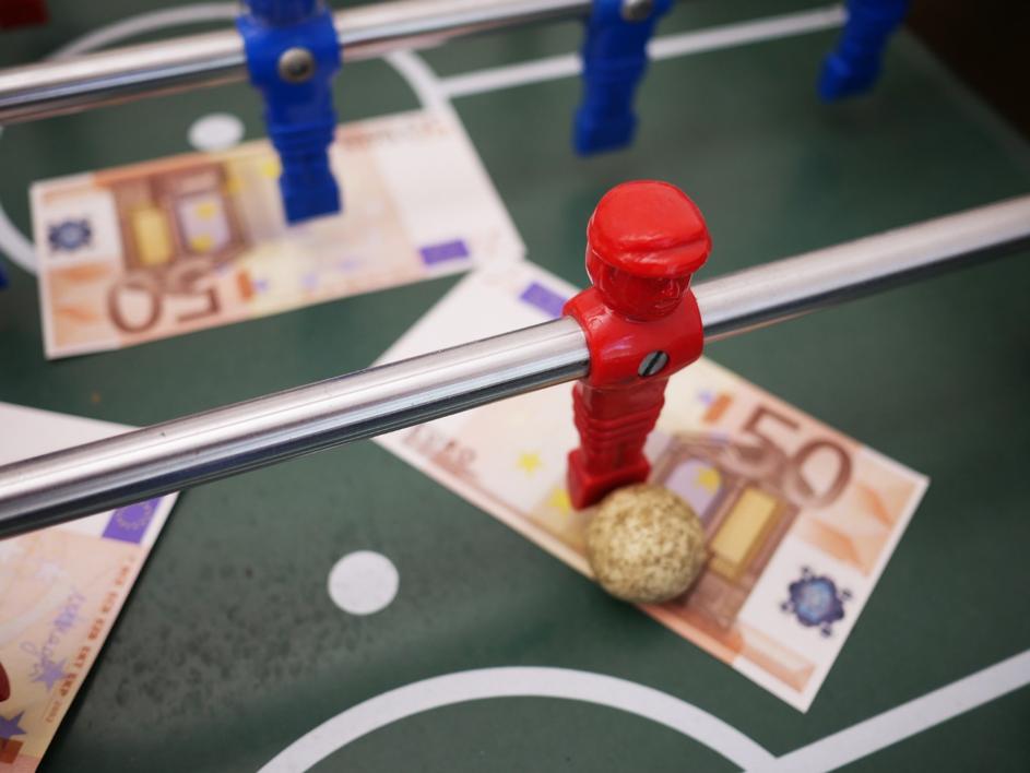 Rotes Männchen eines Tischkickers steht mit Ball auf einem 50-Euro-Schein